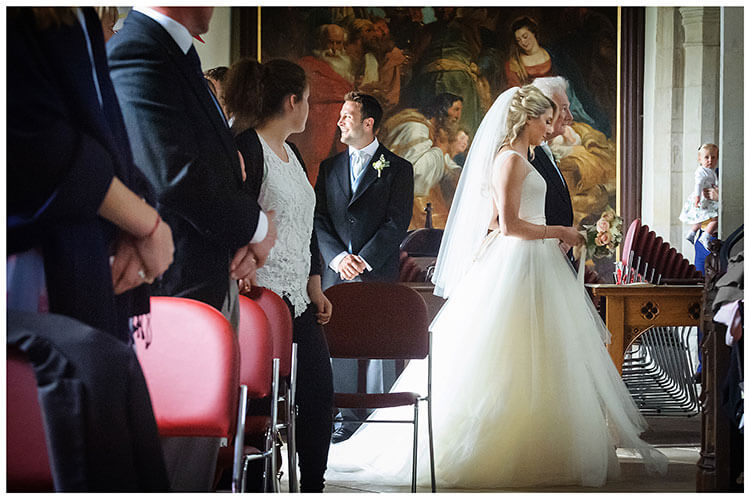 Crishall Church village wedding bride enters church on Fathers arm as guests watch