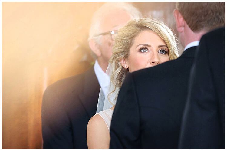 Bride looks at Groom during wedding ceremony at Crishall Cambridgeshire Village Church