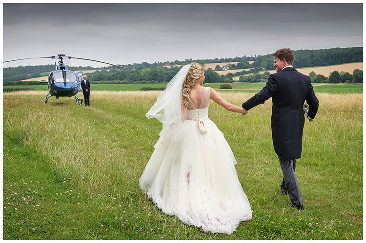 Bride groom looking at each other as the walk hand in hand towards helicopter at Crishall Cambridgeshire Village