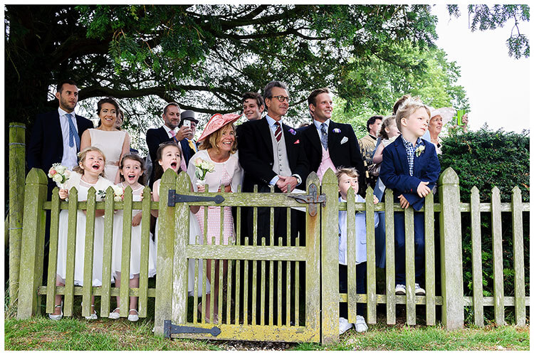 wedding guests watching as bride groom leave Crishall Cambridgeshire Village church in a helicopter