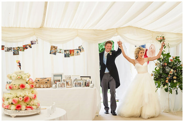 cheering Bride & groom enter the marquee at Crishall Cambridgeshire Village wedding