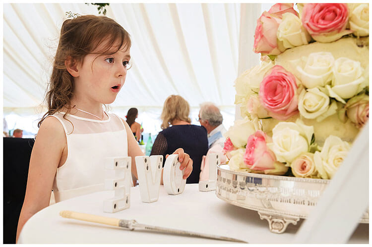 Crishall Cambridgeshire Village wedding flower girl looking at wedding cake as she holds letter L of the word Love