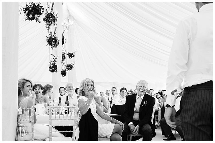 Crishall Cambridgeshire Village wedding in a marquee laughing at grooms speech