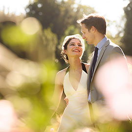 A smiling Bride stares lovingly at her groom in the gardens during Clare College wedding celebrations