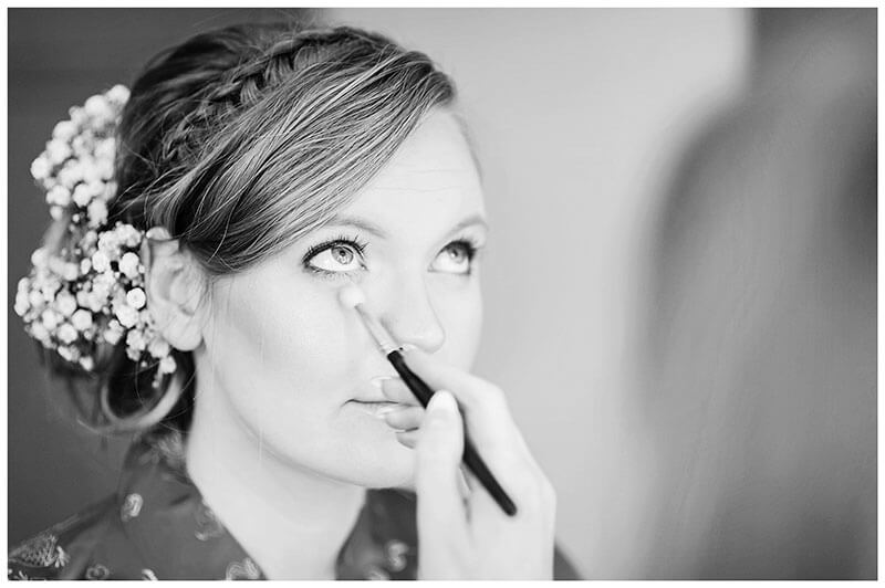 Bride looking up as make up artist applies make up around brides eyes