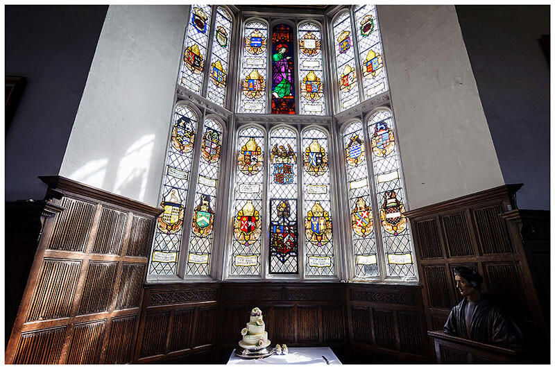 Wedding Cake under large stain glass window during St Johns College wedding in Cambridge