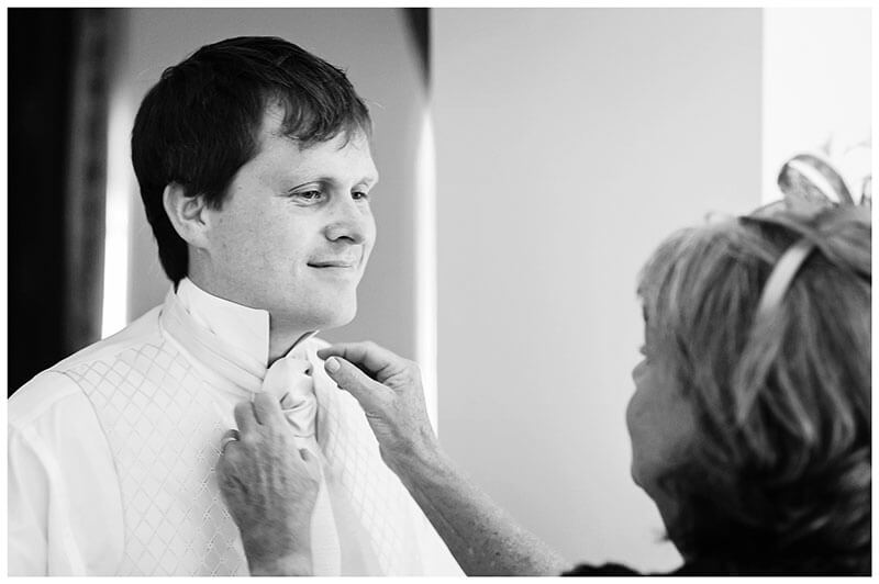 As groom gets ready he has his cravat adjusted by his mother