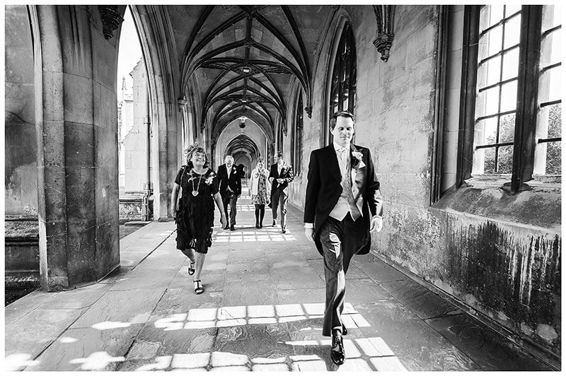 Groom leading the way through st Johns College Cambridge as they head for the wedding ceremony
