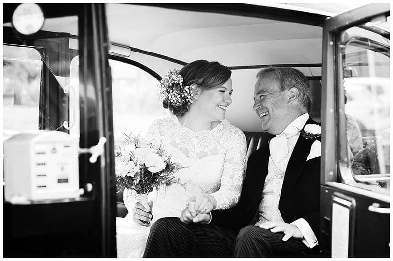 Smiling Bride and father looking at each other as they sit in wedding car