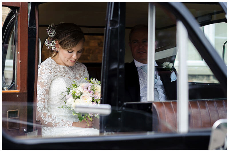 Thoughtful Bride arrives in wedding car sat next to father viewed through open door window