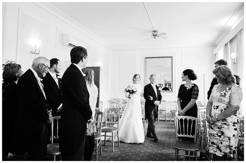 Bride enters wedding ceremony on the arm of her father at Cambridge registry office groom and guest all looking towards