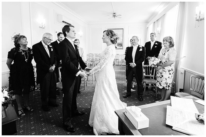 Bride groom hold hands during wedding ceremony at Cambridge registry office