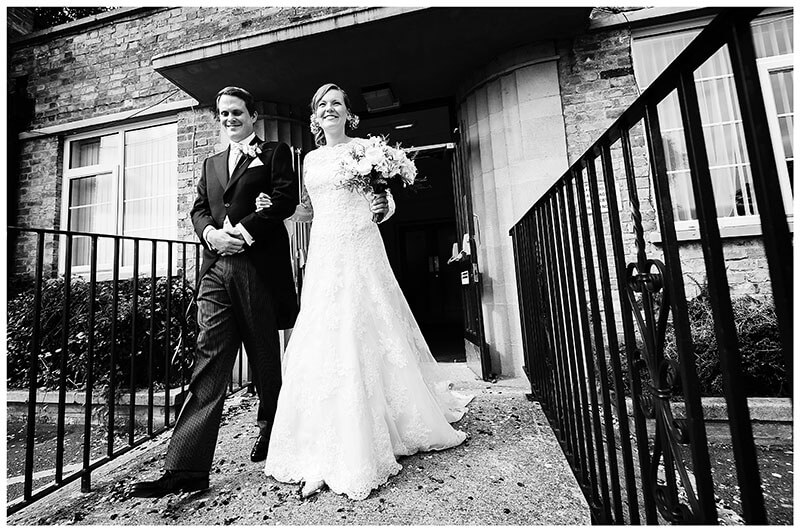 smiling Bride & Groom outside Cambridge registry office after wedding ceremony