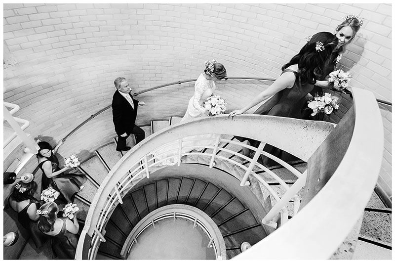 Bridal Party walking up round stairs on way to humanist wedding ceremony at Murray Edwards College Cambridge
