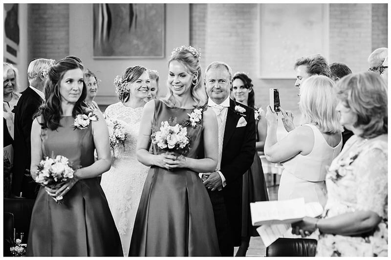 Bride smiles for guest phone photo as bridal party walks down aisle for humanist wedding ceremony at Murray Edwards College Cambridge