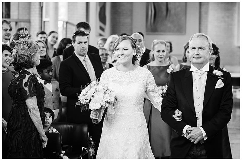Bride smiles as she sees groom as she walks down the aisle on her fathers arm for humanist wedding ceremony at Murray Edwards College Cambridge