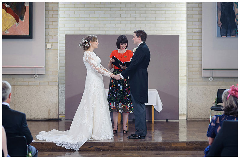 Bride groom gaze at each other during humanist wedding ceremony at Murray Edwards College Cambridge