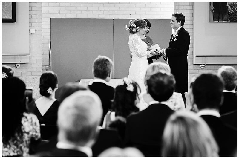 Bride places ring on grooms finger during humanist wedding ceremony at Murray Edwards College Cambridge