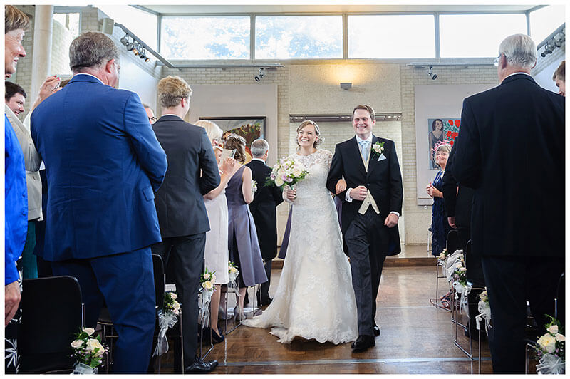 Smiling bride and groom walking down Aisle after humanist wedding ceremony at Murray Edwards College Cambridge