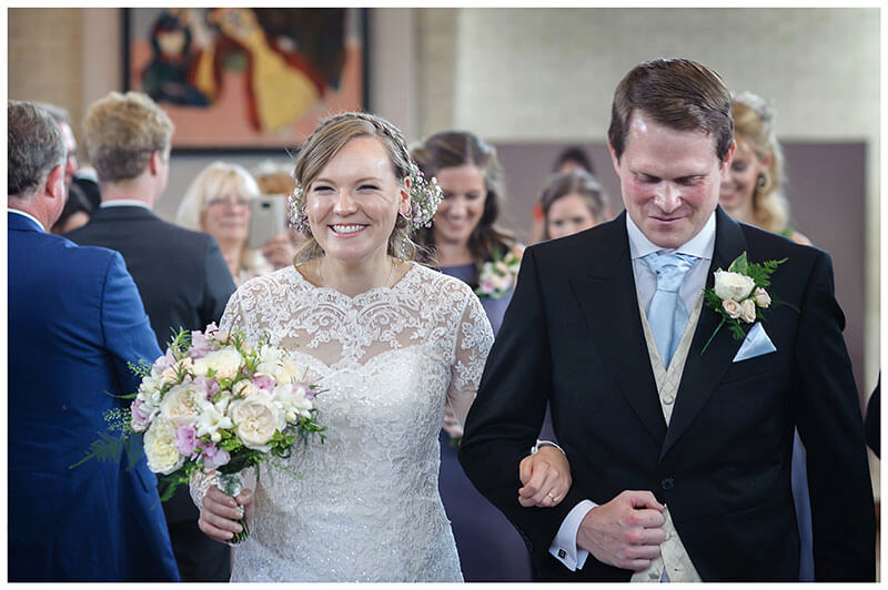 Estatic bride holding bouquet on arm of groom after humanist wedding ceremony at Murray Edwards College Cambridge