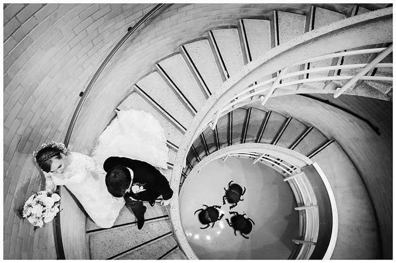 Bride groom walking down spiral staircase with fake beetles at bottom after humanist wedding ceremony at Murray Edwards College Cambridge