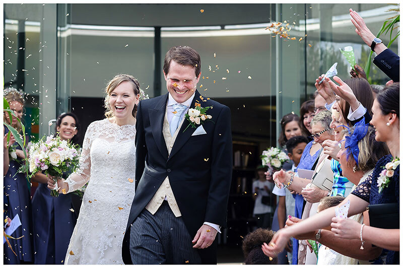 smiling bride groom during confetti throwing after humanist wedding ceremony at Murray Edwards College Cambridge