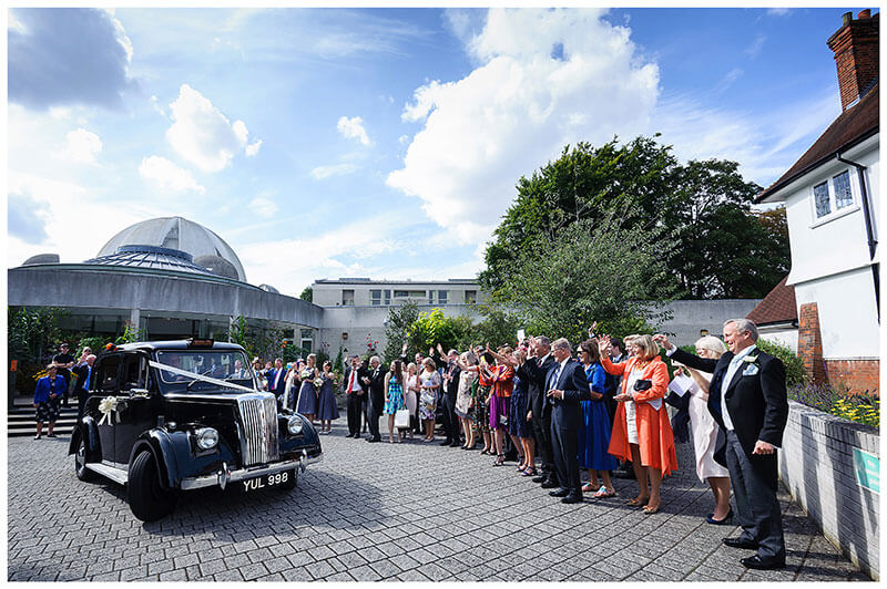 bride groom waved off in old black cab by guests after humanist wedding ceremony at Murray Edwards College Cambridge