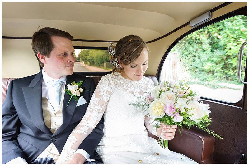 Bride looks at her flowers as groom looks at bride while sat in back of wedding car