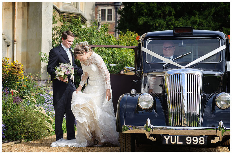 Bride adjusts dress as she is helped out of wedding car old black cab by groom holding brides bouquet at St Johns College Cambridge