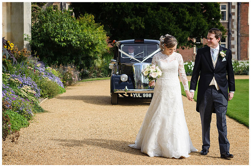 bride groom hold hands as they walk along path in St Johns College Cambridge followed by old black cab wedding car