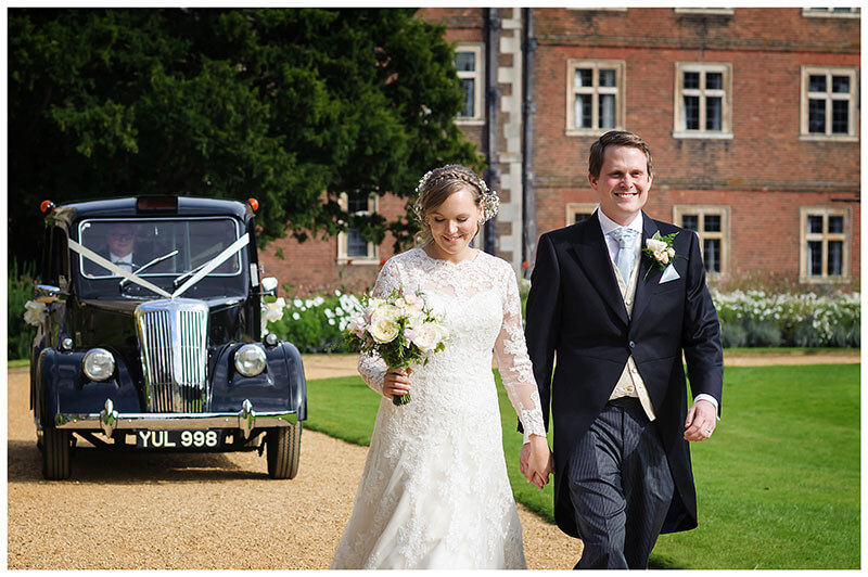 smiling groom and bride in St Johns College Cambridge garden bride looking at her bouquet their wedding car a black taxi in background