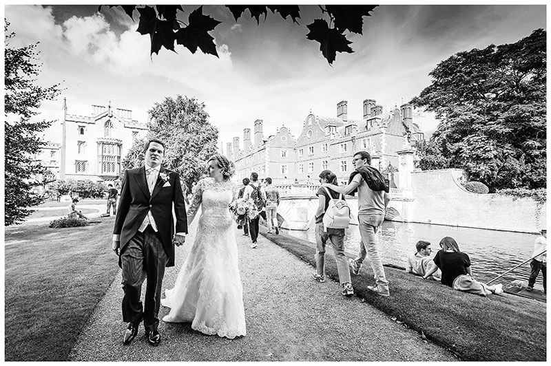 bride groom walking along the river cam in St Johns College Cambridge watched by tourists