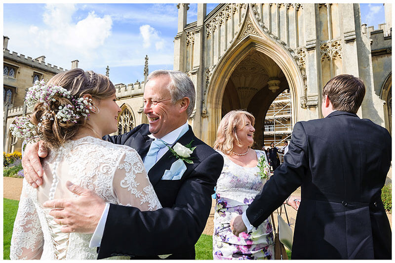 Smile for the bride and groom from brides parents in front St Johns College Cambridge