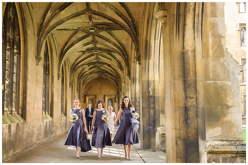 brides maids walking through cloisters of St Johns College Cambridge holding bouquets