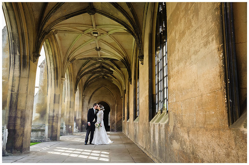 Bride groom kiss in cloisters of St Johns College Cambridge