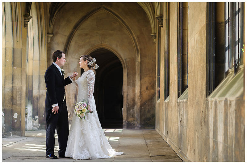 Bride and groom hold hands in cloisters of St Johns College Cambridge