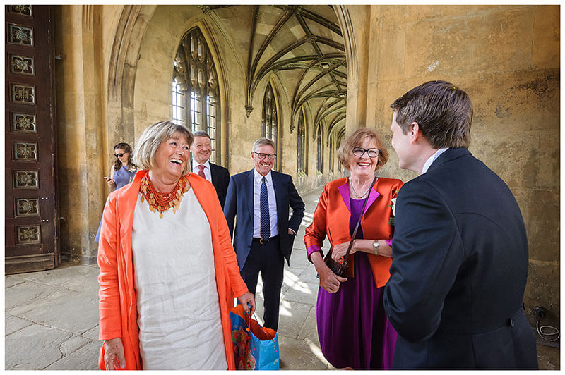 Wedding guests talking and laughing with groom in cloisters St Johns College Cambridge