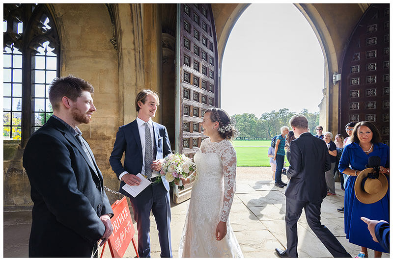 Bride laughing with wedding guests in cloisters of St Johns College Cambridge