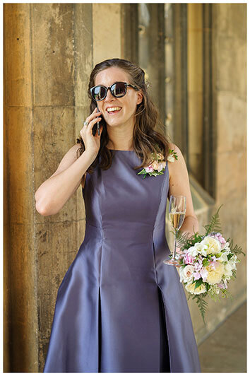 Bridesmaid in purple dress wearing sunglasses holding bouquet and glass of champagne talking on phone in St Johns College Cambridge