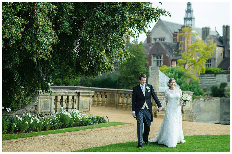 Bride groom walk across lawns of St Johns College Cambridge with bridge behind them