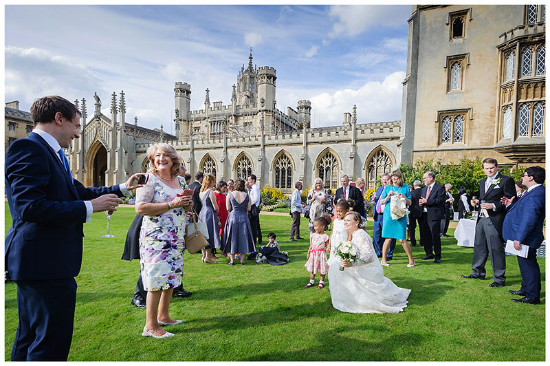 taking a phone photo of bride and yound girls on lawns of St Johns College Cambridge