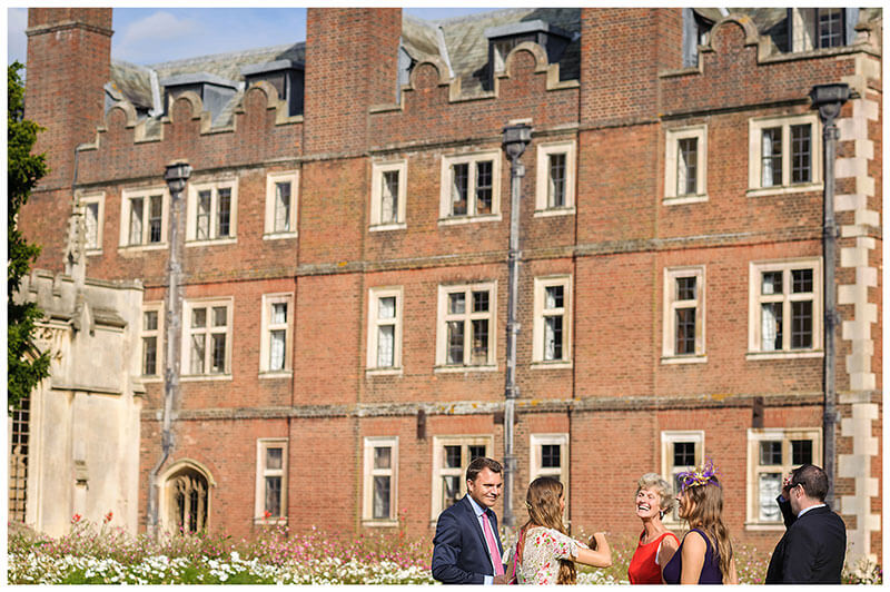 St Johns College wedding reception guests laughing with red brick build in background