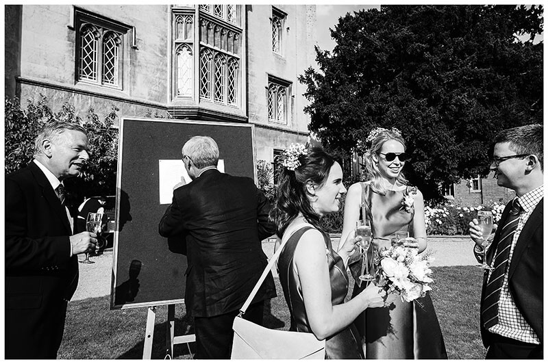 St Johns College wedding reception gentleman checking seating plan while other guests have a convesation