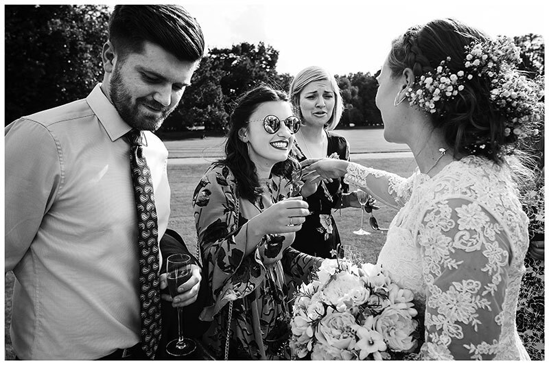 A hug for the bride from female guest in sunglasses during St Johns College wedding reception
