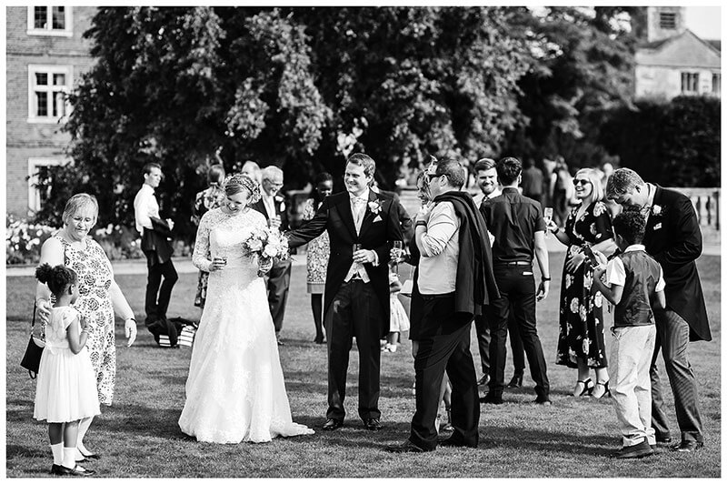 Bride and groom and wedding guests on lawn of St Johns College Cambridge