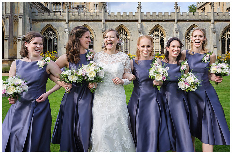 Bride with her bridesmaid linking arms as they walk laughing on lawns of St Johns College Cambridge