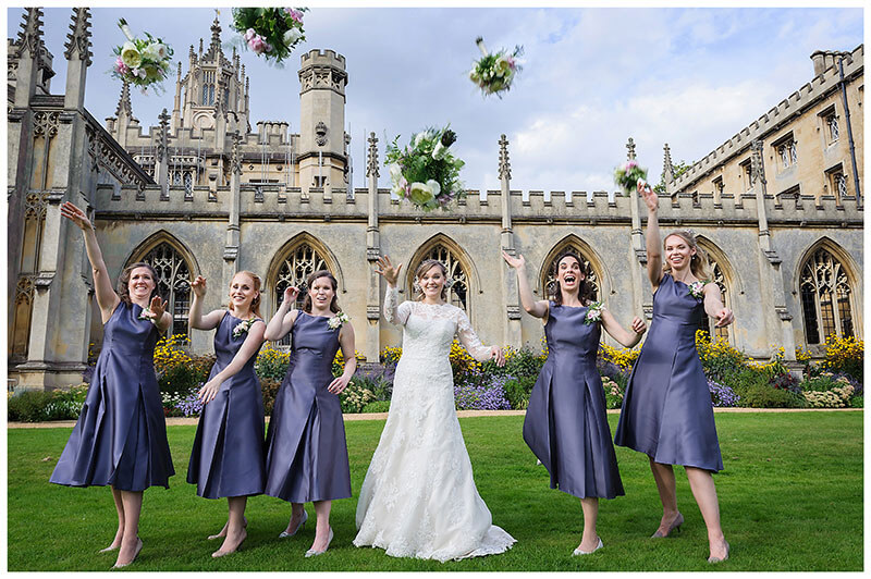 Bride and bridesmaids throwing bouquets on lawns of St Johns College Cambridge