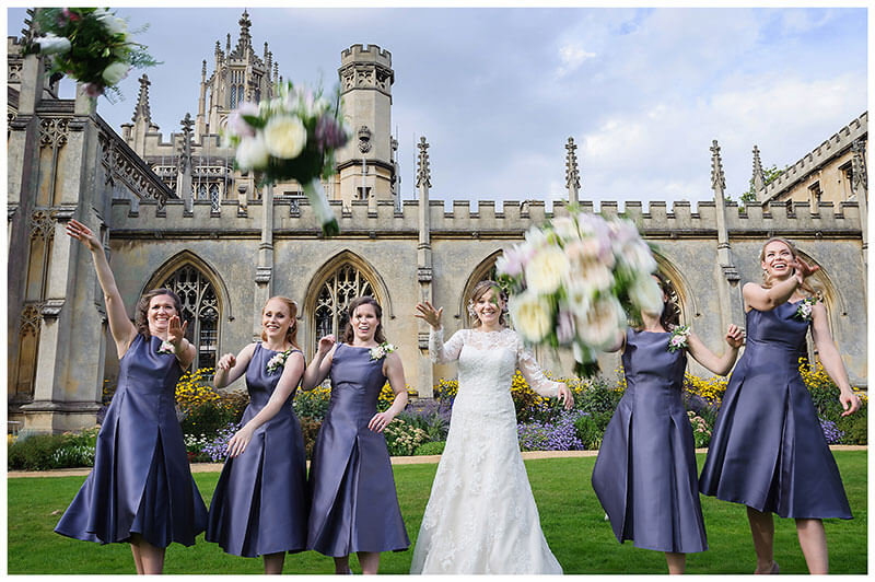 Bride and bridesmaids throw flowers at photographer