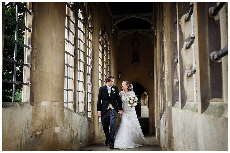 bride groom smile at each other as they walk over St Johns College Bridge of sighs