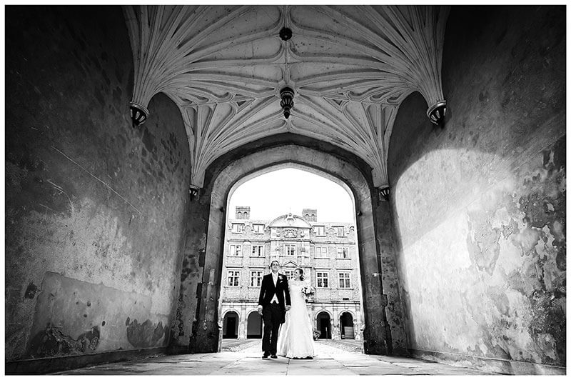 Bride groom walking through grand entrance to second court of St Johns College Cambridge